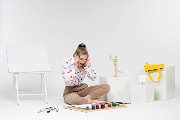 Вид спереди молодая женщина пытается рисовать на белом фоне