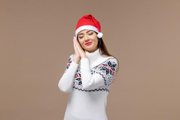 갈색 배경 감정 크리스마스 새 해에 빨간 모자에서 잠을 시도하는 전면보기 젊은 여성