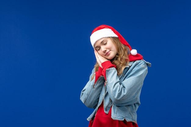 正面図青い背景の感情のクリスマス休暇で眠ろうとしている若い女性