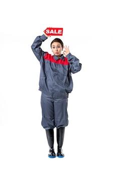 Vista frontale giovane femmina in uniforme che tiene targhetta di vendita rosso su sfondo bianco