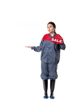Vista frontale giovane femmina in uniforme tenendo la targhetta di vendita su sfondo bianco