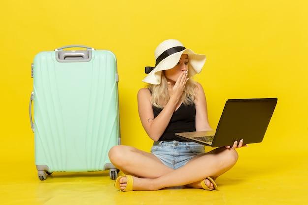 노란색 벽 항해 휴가 여성 여행 여행 태양에 그녀의 노트북을 사용하는 전면보기 젊은 여성