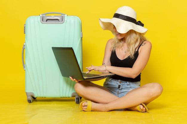노란색 벽 소녀 항해 여행 휴가 여행 태양에 노트북을 사용하는 전면보기 젊은 여성
