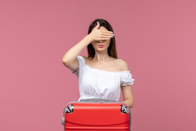 Front view young female in vacation covering her eyes on pink background abroad sea journey voyage travel trip