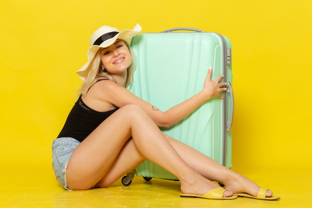 Front view young female in vacation sitting hugging her green bag feeling happy on yellow wall color girl female journey trip sea