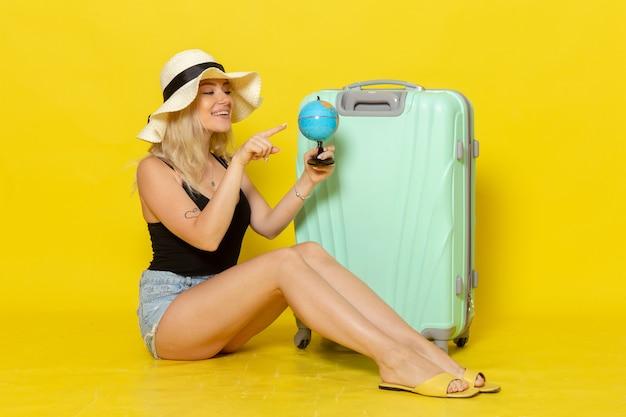 Giovane femmina di vista frontale in vacanza che si siede con il suo globo verde della tenuta della borsa sulla parete gialla viaggio femminile viaggio mare colore sole