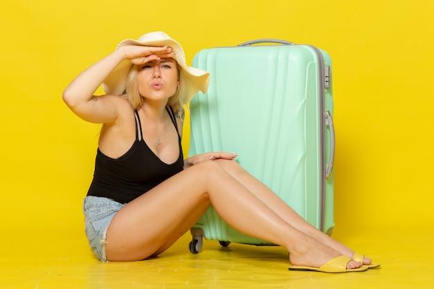 Giovane femmina di vista frontale in vacanza che si siede con la sua borsa verde sul mare del sole di viaggio femminile di viaggio di colore della parete gialla