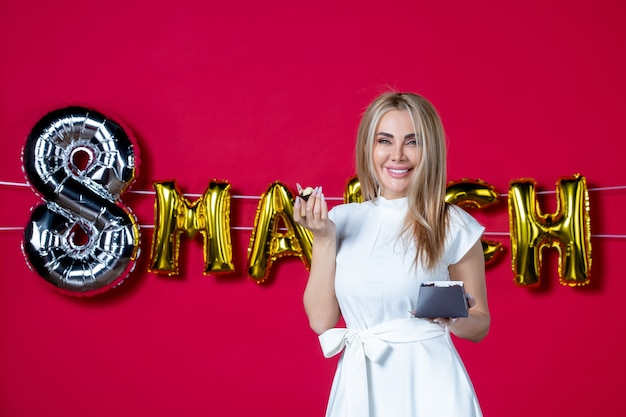Front view young female in white dress holding chocolate candies on decorated red womens day