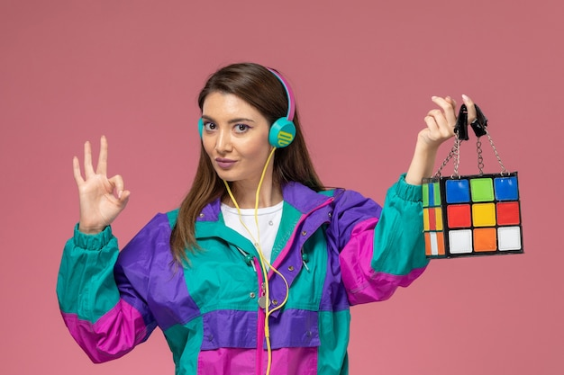 Front view young female in white shirt colored coat listening to music and holding bag on pink wall, color woman pose model