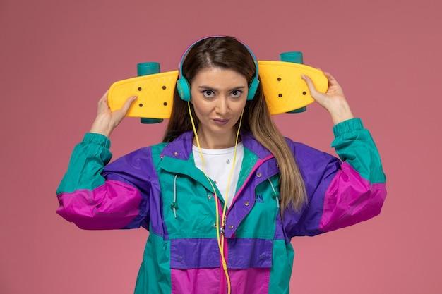 Giovane femmina di vista frontale in cappotto colorato della camicia bianca che ascolta lo skateboard della tenuta di musica sulla parete rosa, modello di posa della donna di colore