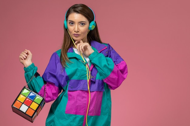 Front view young female in white shirt colorful coat listening to music, photo color woman pose model