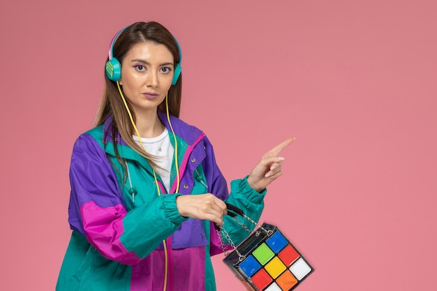 Front view young female in white shirt colorful coat listening to music