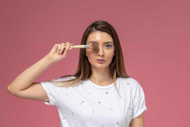 Giovane femmina di vista frontale in camicia bianca che copre l'occhio con la spazzola sulla bellezza della donna di modello rosa della parete