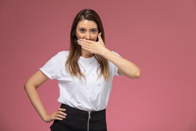Giovane femmina di vista frontale in camicia bianca che copre la bocca con il sorriso