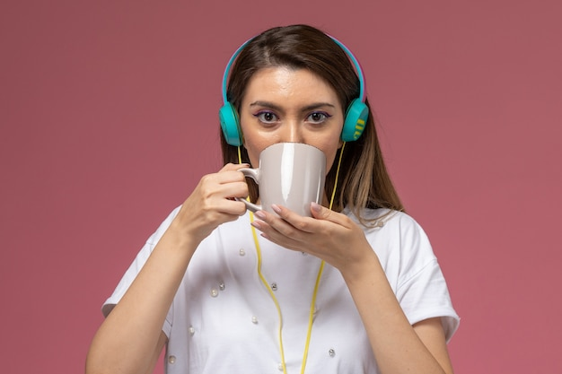 Front view young female in white shirt drinking coffee listening to music on the pink wall model woman