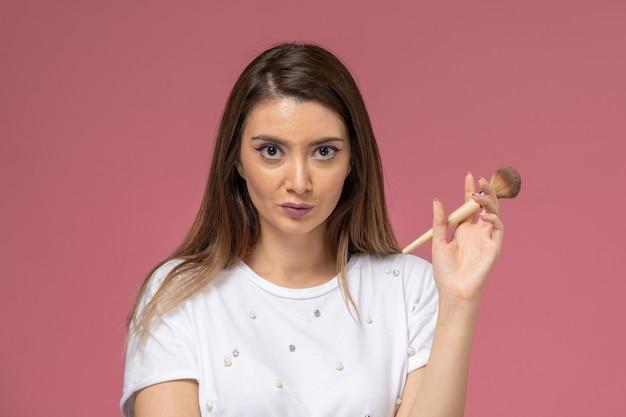 Giovane femmina di vista frontale in camicia bianca che tiene la spazzola per il trucco, donna di posa di modello della donna di colore