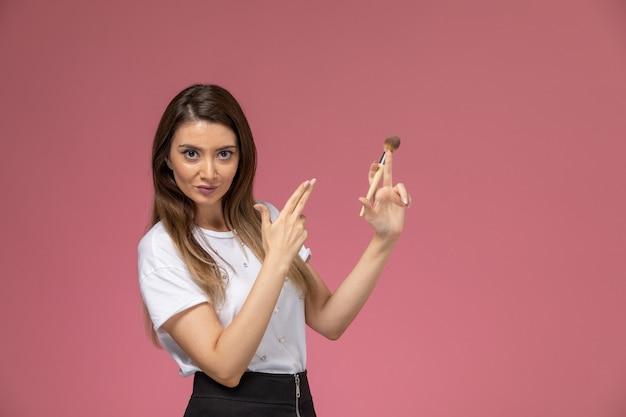 Giovane femmina di vista frontale in camicia bianca che tiene la spazzola per trucco sulla bellezza della donna di modello della parete rosa