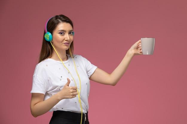 Giovane donna di vista frontale in camicia bianca che tiene tazza e ascolto di musica