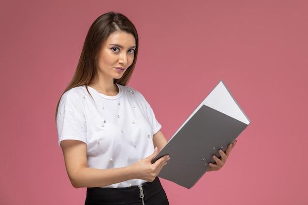 Giovane femmina di vista frontale in camicia bianca che tiene documento grigio sulla parete rosa, modello di posa della donna di colore