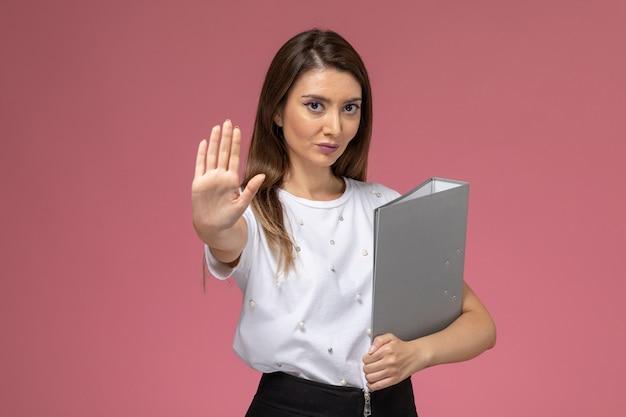 Giovane femmina di vista frontale in camicia bianca che tiene file grigio sul muro rosa, donna di posa della donna di modello