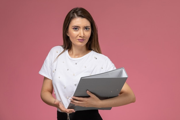 Giovane femmina di vista frontale in camicia bianca che tiene file grigi sulla parete rosa, donna di posa della donna di modello
