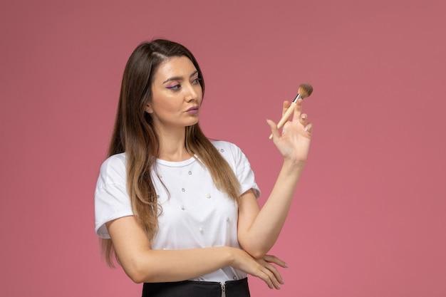 Giovane femmina di vista frontale in camicia bianca che tiene il pennello per il trucco sulla parete rosa, donna di modello di posa della donna di colore