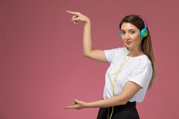 Front view young female in white shirt listening to music on the pink wall, color woman model woman
