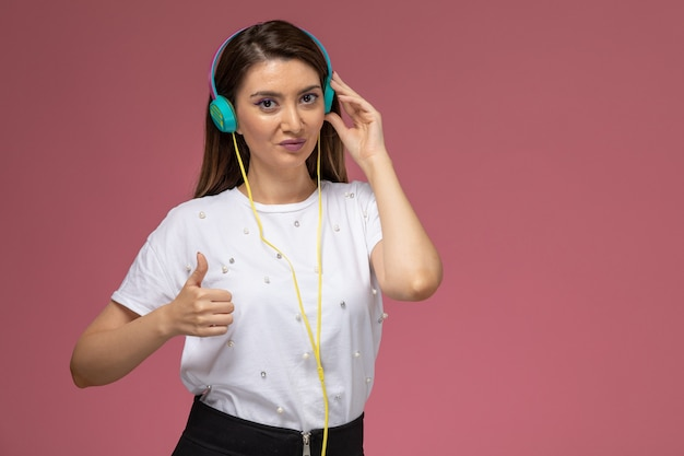 Front view young female in white shirt listening to music via earphones on the pink wall, color woman pose model woman