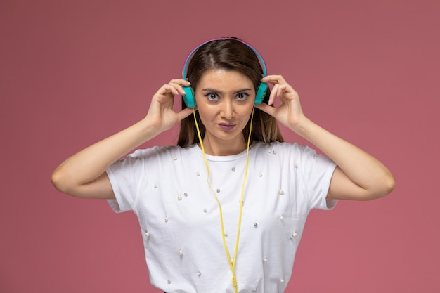 Front view young female in white shirt listening to music via her colored earphones on the pink wall, color woman model posing woman