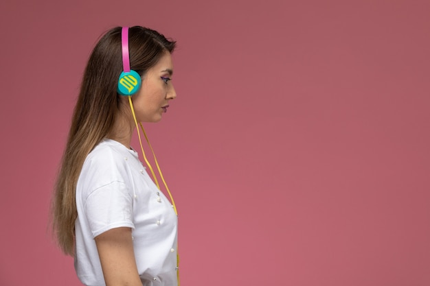 Front view young female in white shirt listening to music with her earphones on the pink wall, color woman pose model woman