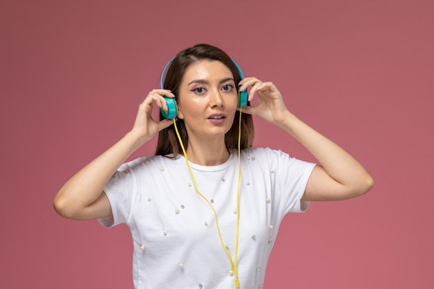Front view young female in white shirt posing and listening to music via her earphones on the pink wall, color woman model posing woman