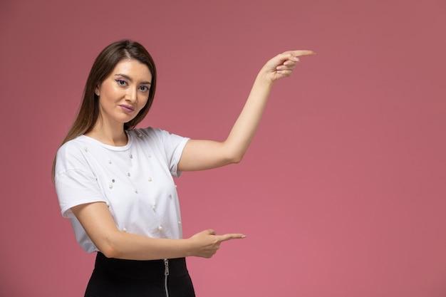 Giovane femmina di vista frontale in camicia bianca che posa sulla parete rosa, modello di posa della donna di colore