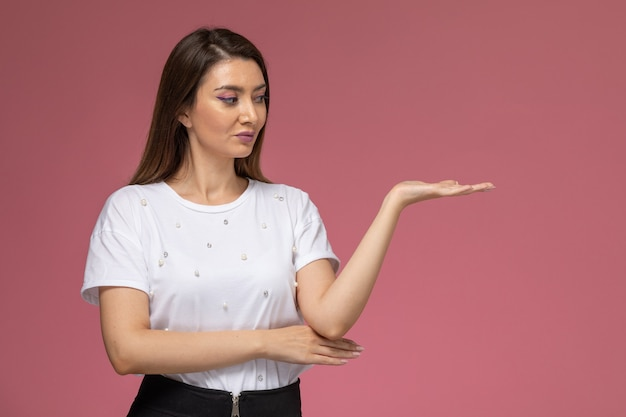 Front view young female in white shirt posing with raised hand on the pink wall, color woman pose model woman