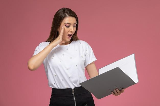 Vista frontale giovane femmina in camicia bianca leggendo file sul muro rosa chiaro, modello donna posa