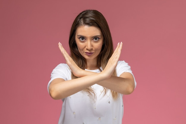 Front view young female in white shirt showing ban sign on the pink wall, color woman model woman