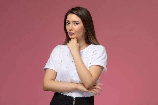 Vista frontale giovane femmina in camicia bianca in piedi in posa sul muro rosa, modello donna posa donna
