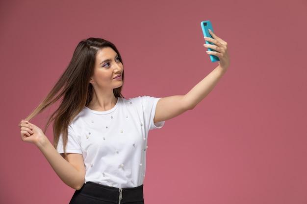 Giovane femmina di vista frontale in camicia bianca che prende un selfie sulla parete rosa, posa della donna di modello