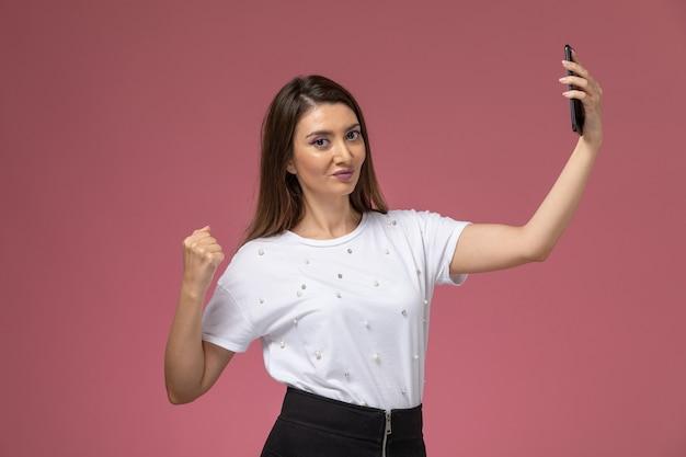 Giovane femmina di vista frontale in camicia bianca che prende un selfie sulla parete rosa, donna di modello