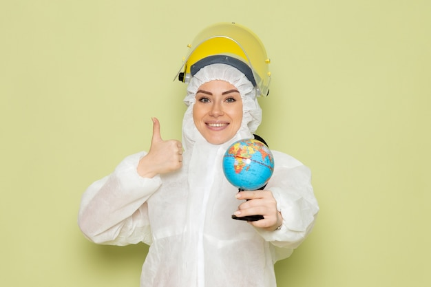 Front view young female in white special suit and yellow helmet holding little globe with slight smile on the green space chemistry work