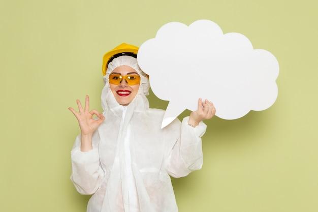 Giovane femmina di vista frontale in vestito speciale bianco e casco giallo che tiene segno bianco sul lavoro di chimica dello spazio verde