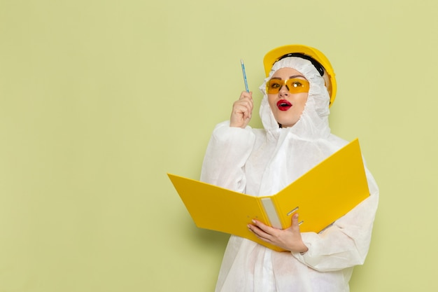 Front view young female in white special suit and yellow helmet holding yellow files and writing down on the green space chemistry work suit uniform science