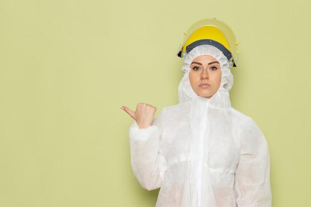 Giovane femmina di vista frontale in vestito speciale bianco e casco giallo che posano appena sul lavoro dello spazio verde