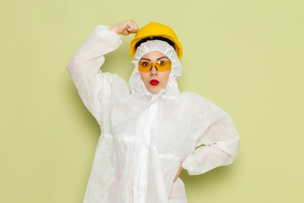Front view young female in white special suit and yellow helmet posing on the green floor job