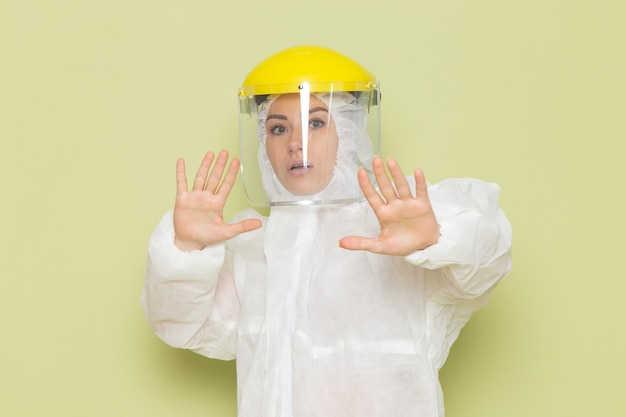 Front view young female in white special suit and yellow helmet posing with caution on the green space suit uniform science