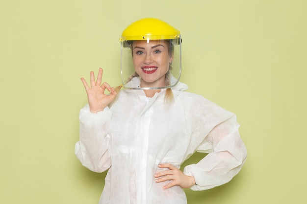 Front view young female in white special suit and yellow helmet posing with smile on the green space job