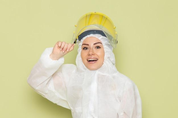 Giovane femmina di vista frontale in vestito speciale bianco e casco giallo che posa con il sorriso sul lavoro di scienza uniforme dello spazio verde
