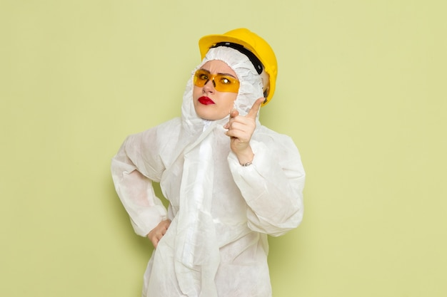 Front view young female in white special suit and yellow helmet threatening with finger on the green space job
