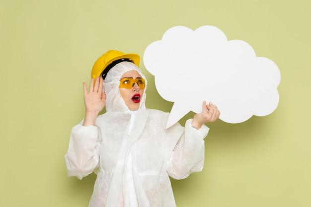 Giovane donna di vista frontale in vestito speciale bianco e casco protettivo giallo che tiene grande segno bianco sulla scienza uniforme della tuta spaziale verde