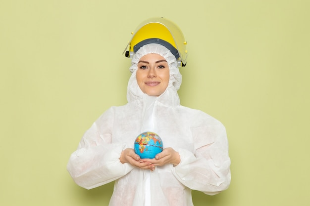 Front view young female in white special suit and yellow protective helmet holding little round globe with slight smile on the green space