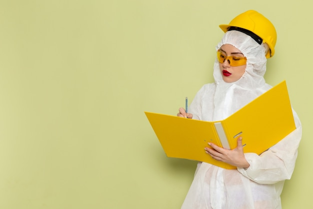 Front view young female in white special suit and yellow protective helmet holding yellow files on the green space suit uniform science